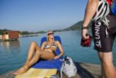 Das Foto zeigt eine Frau im Liegestuhl am See